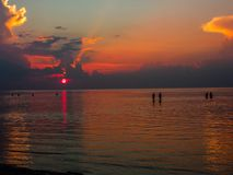 Siluetas de la gente que camina en el mar en el fondo de la puesta del sol foto de archivo libre de regalías