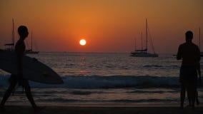 Siluetas de la gente que camina a lo largo de la playa en la puesta del sol Naves en el horizonte almacen de video