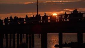 Siluetas de la gente que caminan a lo largo del embarcadero en la puesta del sol dramática en día de verano caliente en la playa  almacen de video