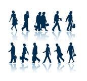 Siluetas de la gente que recorren Imagen de archivo libre de regalías