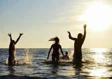 Siluetas de la gente que salta en el océano Fotografía de archivo libre de regalías