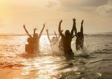 Siluetas de la gente que salta en el océano Imágenes de archivo libres de regalías
