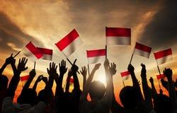 Siluetas de la gente que sostiene la bandera de Indonesia foto de archivo libre de regalías
