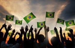 Siluetas de la gente que sostiene la bandera del Brasil Imágenes de archivo libres de regalías