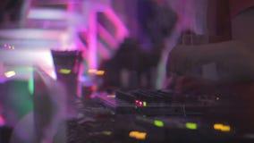 Siluetas de la gente que va de fiesta, manos del disk jockey de sexo masculino que juegan música en club metrajes