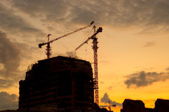 Siluetas de la grúa de la construcción de viviendas imagen de archivo libre de regalías