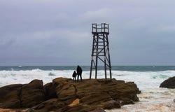 Siluetas de la hija y del padre en rocas por la torre del salvavidas que mira hacia fuera al mar tempestuoso fotografía de archivo libre de regalías