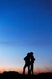 Siluetas de la madre y de la hija en la puesta del sol hermosa oscuridad Fotos de archivo