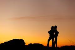 Siluetas de la madre y de la hija en la puesta del sol hermosa oscuridad Imagen de archivo libre de regalías