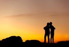 Siluetas de la madre y de la hija en la puesta del sol hermosa oscuridad Foto de archivo libre de regalías