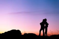 Siluetas de la madre y de la hija en la puesta del sol hermosa oscuridad Fotos de archivo libres de regalías