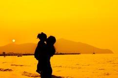 Siluetas de la madre y del bebé que se besan en puesta del sol Imágenes de archivo libres de regalías