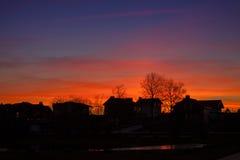 Siluetas de la puesta del sol de las casas Imágenes de archivo libres de regalías