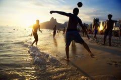 Siluetas de la puesta del sol que juegan al fútbol el Brasil de la playa de Altinho Futebol Fotos de archivo