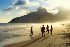 Siluetas de la puesta del sol que juegan al fútbol el Brasil de la playa de Altinho Futebol Imágenes de archivo libres de regalías