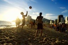 Siluetas de la puesta del sol que juegan al fútbol Río de la playa de Altinho Futebol Foto de archivo