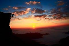 Siluetas de la subida de la montaña con el fondo de la puesta del sol Fotografía de archivo libre de regalías
