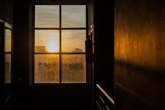 Siluetas de la ventana de cristal sucia con el fondo de la puesta del sol Foto de archivo libre de regalías