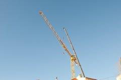 Siluetas de las grúas de construcción en el cielo Imagen de archivo