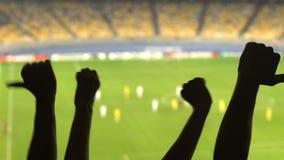 Siluetas de las manos de los fanáticos del fútbol que muestran los pulgares abajo, juego descontentado gente almacen de metraje de vídeo