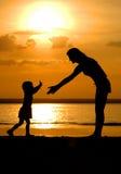 Siluetas de las mujeres y del niño en ocaso Foto de archivo libre de regalías