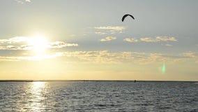 Siluetas de las personas que practica surf de la cometa en la puesta del sol Kiter en el mar Costa de Montenegro y mar adriático