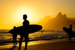 Siluetas de las personas que practica surf que sostienen sus tablas hawaianas en el fondo de la puesta del sol de oro en la playa imagen de archivo