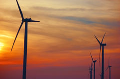 Siluetas de las turbinas de viento en un parque eólico en la puesta del sol Foto de archivo libre de regalías