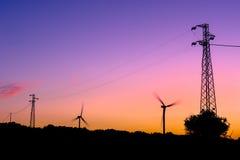 Siluetas de las turbinas de viento y de los pilones de la electricidad fotos de archivo