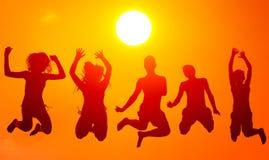 Siluetas de los adolescentes y de las muchachas que saltan arriba en el aire encendido Imágenes de archivo libres de regalías