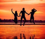 Siluetas de los amigos jovenes felices que saltan en Fotos de archivo libres de regalías
