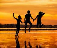 Siluetas de los amigos jovenes felices que saltan en Foto de archivo