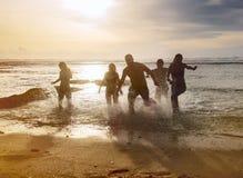 Siluetas de los amigos que corren fuera del océano Imágenes de archivo libres de regalías