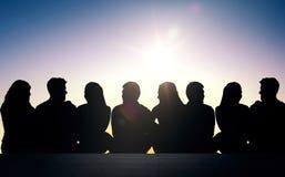 Siluetas de los amigos que se sientan en las escaleras sobre el sol Imagenes de archivo