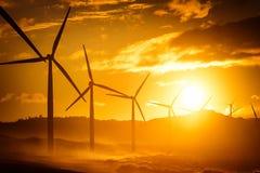 Siluetas de los generadores de poder de la turbina de viento en la costa costa del océano Imagen de archivo