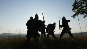 Siluetas de los guerreros de Vikingos que luchan con las espadas, escudos Contre-jour metrajes