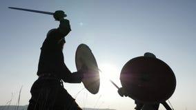 Siluetas de los guerreros de Vikingos que luchan con las espadas, escudos Contre-jour almacen de metraje de vídeo