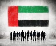 Siluetas de los hombres de negocios que miran la bandera de los UAE Fotos de archivo libres de regalías