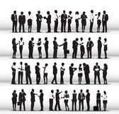 Siluetas de los hombres de negocios que trabajan en fila Foto de archivo