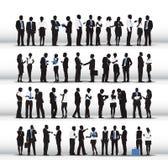 Siluetas de los hombres de negocios que trabajan en fila Fotos de archivo libres de regalías