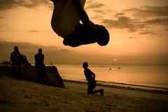 Siluetas de los hombres que se resuelven en la playa Imágenes de archivo libres de regalías