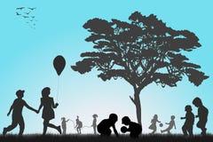 Siluetas de los niños que juegan afuera Foto de archivo libre de regalías