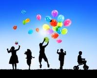 Siluetas de los niños que juegan al aire libre junto Imágenes de archivo libres de regalías