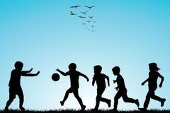 Siluetas de los niños que juegan a fútbol Imagen de archivo libre de regalías