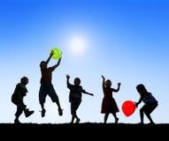Siluetas de los niños que juegan los globos al aire libre Foto de archivo libre de regalías