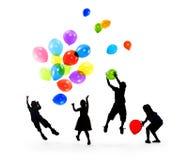 Siluetas de los niños que juegan los globos juntos Foto de archivo