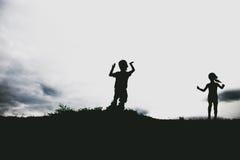 Siluetas de los niños que saltan de un acantilado de la arena en la playa Fotografía de archivo libre de regalías