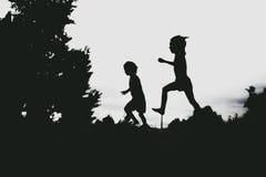 Siluetas de los niños que saltan de un acantilado de la arena en la playa Foto de archivo