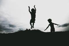 Siluetas de los niños que saltan de un acantilado de la arena en la playa Foto de archivo libre de regalías