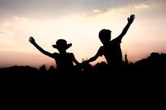 Siluetas de los niños que saltan de un acantilado en la puesta del sol Foto de archivo
